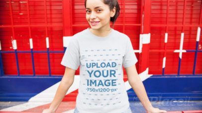 Trendy Young Girl Wearing A Tshirt Video Mockup Sitting Outside British Place a13008