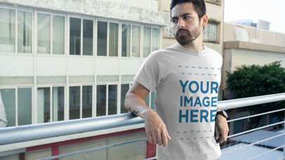 Hipster Guy with a Beard Leaning on a Rail Wearing a Round Neck Tee Video Mockup a12172