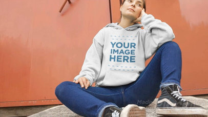 Video of a Woman Sitting Down with Legs Open Wearing a Pullover Hoodie a13116