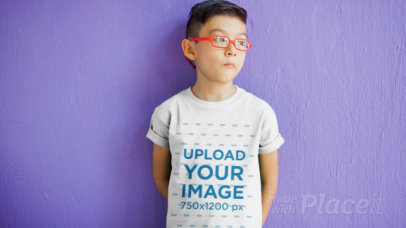 Boy with Glasses Standing in Front of a Purple Wall Wearing a Kid's Tee Video a12539