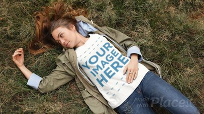 Pretty Girl Lying on the Grass While Wearing a Round Neck T-Shirt Cinemagraph Video Playing With Her Hair a13311