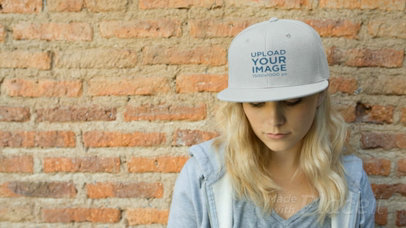 Young Woman Wearing a Snapback Hat Video Mockup Standing Against a Bricks Wall a14139