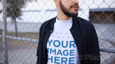 Nice Looking Guy Using T-Shirt Video Against a Fence a13472