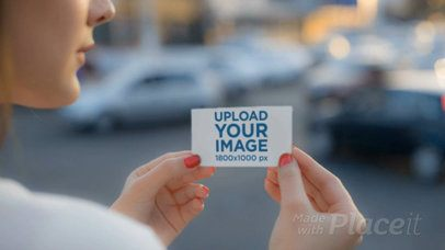 Pretty Girl Holding A Business Card Video Mockup in the City While Cars Passing By a13919