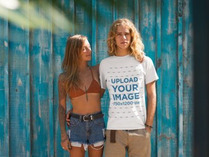 Surfer Guy Wearing a T-Shirt Mockup Hugging his Girlfriend Near a Blue Wall a18807