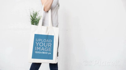 Stop Motion of a Tote Bag Being Held by a Girl Walking by a White Wall a13762