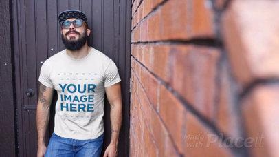 Hispter Dude Wearing a T-Shirt Video Standing Against a Black Door a12262