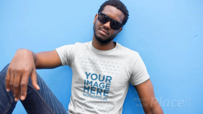 Young Black Man with Sunglasses Wearing a T-Shirt Video Sitting on the Sidewalk a12117