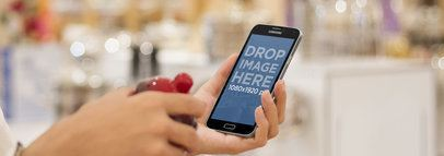 Samsung Galaxy S5 Mockup Featuring a Woman at a Decor Store Wide