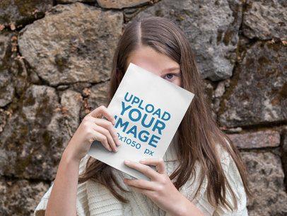 Girl Hiding Behind a Book Mockup Outdoors a19085