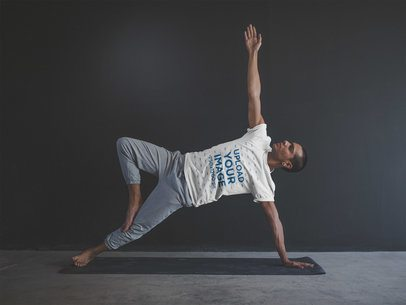 Man Doing a Side Plank Pose Wearing a T-Shirt Mockup on his Yoga Mat a19966