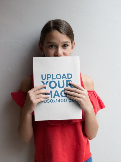 Happy Girl Holding her New Book Mockup Against a White Wall a19083