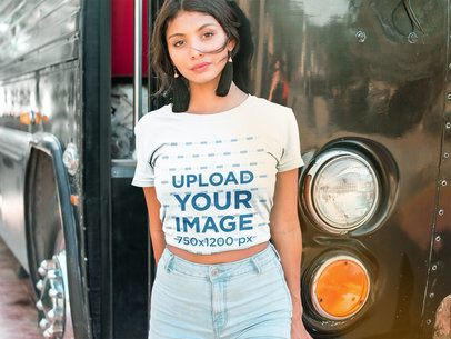 Latina Woman Wearing a T-Shirt Mockup Leaning Against a Vintage Bus a18842