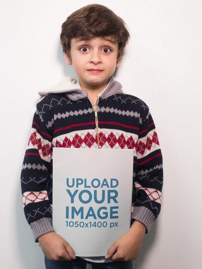 Surprised Boy Holding a Book Mockup Against a White Wall a19219