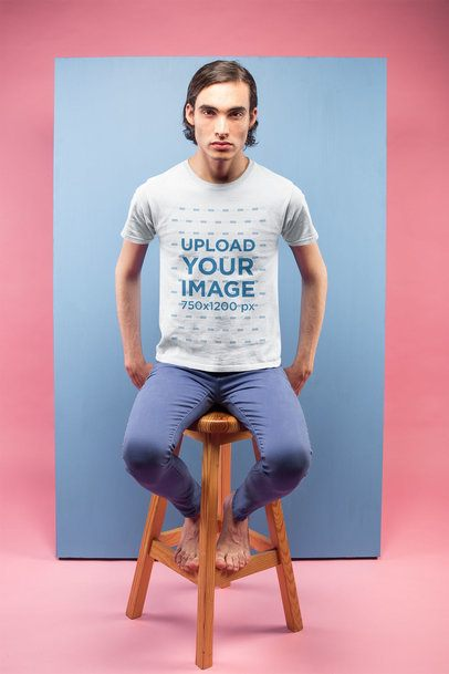 T-Shirt Mockup of a Man Sitting Against a Light Blue Rectangle in a Pink Room a19668