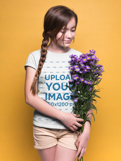 Girl Holding Purple Flowers Wearing a T-Shirt Mockup Against an Orange Background a19591