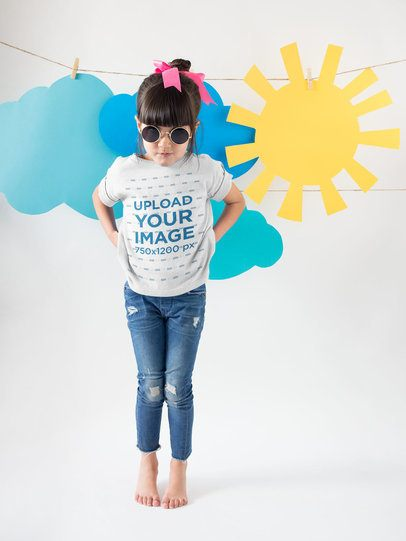 Little Girl Wearing a Tshirt Mockup Making Faces Against Cardboard Clouds and Sun a19479