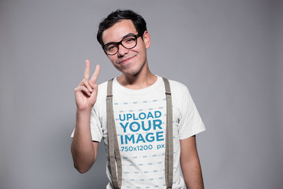 Smiling Nerd Wearing a T-Shirt Mockup and Suspenders Doing the Peace Sign a19356