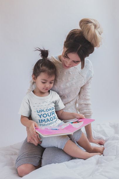 Girl Reading a Book Wearing a T-Shirt Mockup with her Mom Sitting on Bed a20285