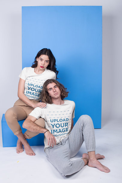 Tshirts Mockup Being Worn by an Interracial Couple Relaxing Against a Light Blue Rectangle a19924
