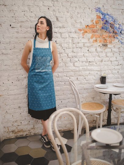 Girl Wearing an Apron Mockup Against a White Bricks Wall a19821