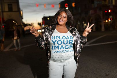 Woman Wearing a Plus Size T-shirt Mockup Near a Venice Sign a18305