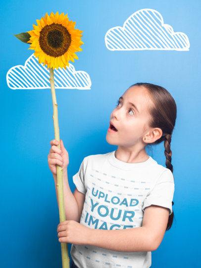 Little Girl Holding a Big Sunflower Wearing a T-Shirt Mockup Against a Blue Wall with Clouds a19816