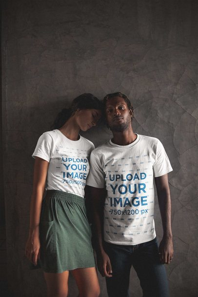 Posing Interracial Couple Wearing T-Shirts Mockup Against a Gray Wall a20112