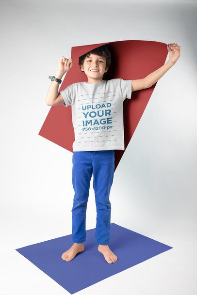 Kid Holding a Paper Wearing a T-Shirt Mockup in a White Room a19490