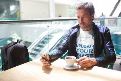 Middle Age Man Wearing a T-Shirt Mockup and a Leather Jacket at a Cafe a20313