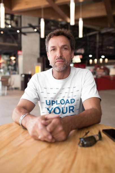 Middle-Aged Man Wearing a T-Shirt Mockup Sitting at a Cafe a20312