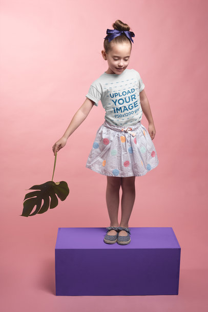 Little Girl Playing with a Leaf Wearing a T-Shirt Mockup on a Box a19731