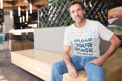 Middle-Aged Man Wearing a T-Shirt Mockup at a Restaurant a20314