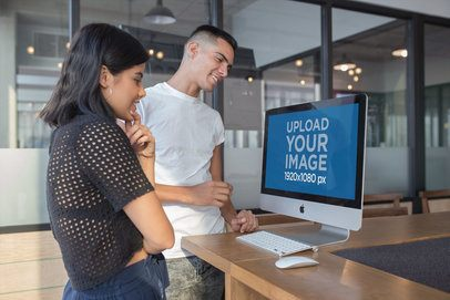 Man and Woman Looking at an iMac Mockup in a Modern Office a20764