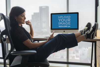 Girl Checking her Phone at the Office Near an iMac Mockup 20761