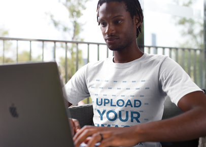 Black Man with Short Dreadlocks Wearing a Tshirt Mockup While Working with his Laptop a20528