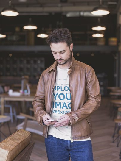Man Wearing a Tshirt Mockup and a Brown Leather Jacket Sending a Text Message a20392