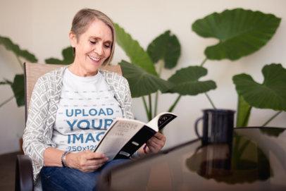 Smiling Senior Woman Wearing a Tshirt Mockup Reading a Book a20660