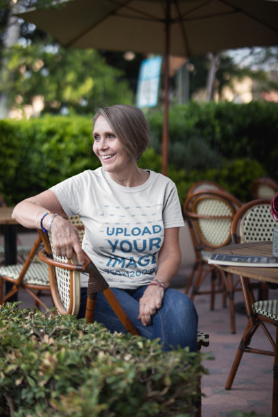 Smiling Senior Lady Wearing a T-Shirt Mockup at a Cafe a20665