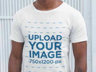Closeup of a Black Man Wearing a T-Shirt Mockup Against a White Metal Door a20903