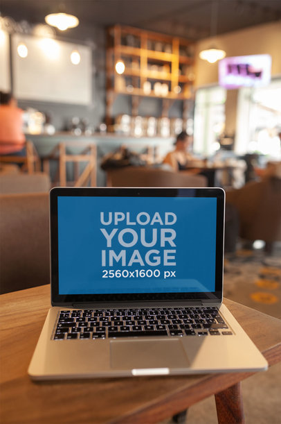 MacBook Mockup Standing on the Corner of a Wooden Table a20998