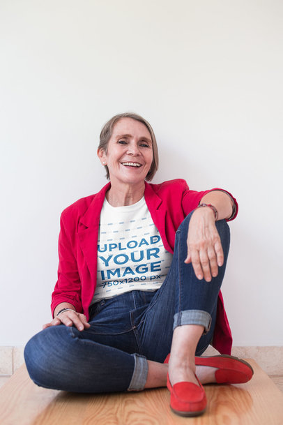 Happy Senior Woman Wearing a T-Shirt Mockup and a Red Blazer Sitting Against a Wall a20670