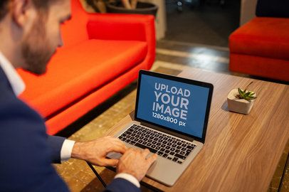 Man Using a MacBook Mockup on a Wooden Coffee Table a21002