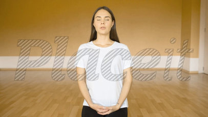 Young Woman Doing Yoga While on an Empty Room with a Book Lying Close to Her Template Video v14172