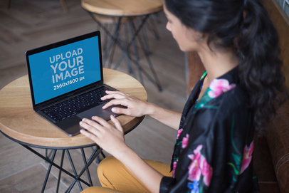 Woman Working on a MacBook Mockup Over a Coffee Table a21168