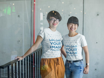 T-Shirt Mockup of Two Women Smiling Behind a Big Window a20438