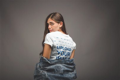 Mockup from the Back of a Girl Removing her Denim Jacket in a Grey Room a20889