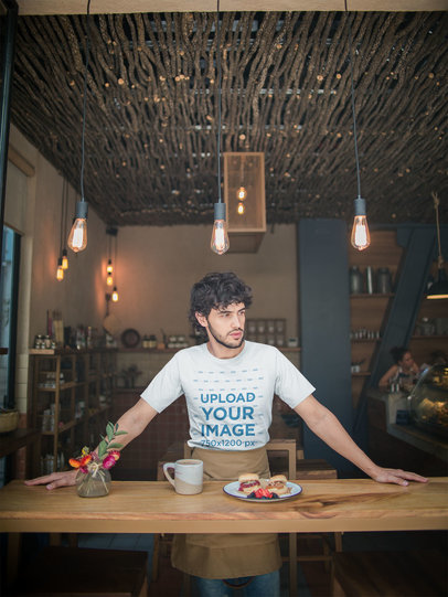 Mockup of a Waiter Wearing a T-Shirt Leaning Against a Wooden Table a20480