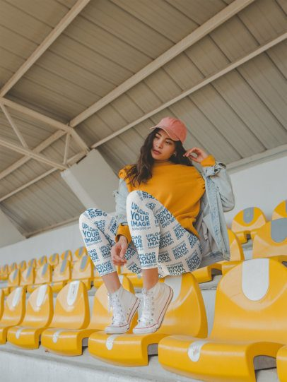 Mockup of a Girl Wearing Leggings while Sitting Over Yellow Seats in a Stadium a19039