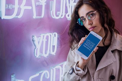 Mockup of a Pretty Woman Holding a Rose Gold iPhone 7 Plus by a Neon Sign a21281